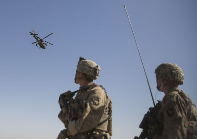 This June 10, 2017 photo released by the U.S. Marine Corpsshows an AH-64 Apache attack helicopter provides security from above while CH-47 Chinooks drop off supplies to U.S. Soldiers with Task Force Iron at Bost Airfield, Afghanistan. Sixteen years into its longest war, the United States is sending another 4,000 troops to Afghanistan in an attempt to turn around a conflict characterized by some of the worst violence since the Taliban were ousted in 2001.