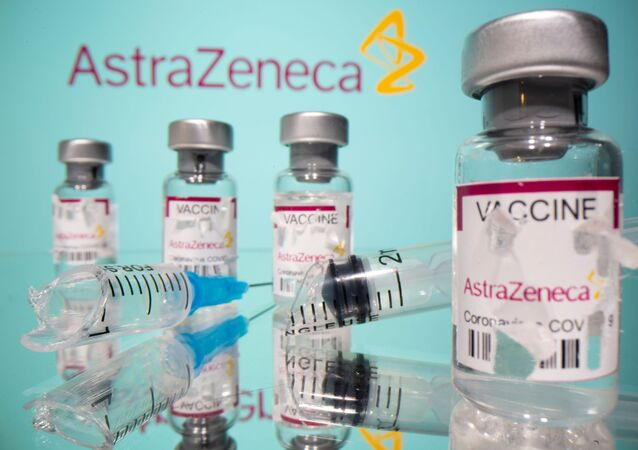 Vials labelled with broken sticker AstraZeneca COVID-19 Coronavirus Vaccine and a broken syringe are seen in front of a displayed AstraZeneca logo in this illustration taken March 15, 2021.