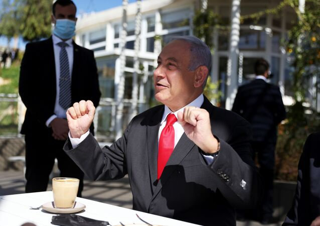 Israel Prime Minister, Benjamin Netanyahu gestures as he sits in a cafe while Israel further eases coronavirus disease (COVID-19) restrictions in Jerusalem March 7, 2021