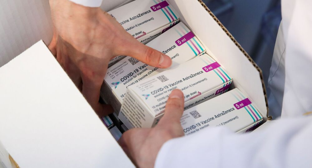 A medical worker unpacks a box of Oxford/AstraZeneca's COVID-19 vaccine