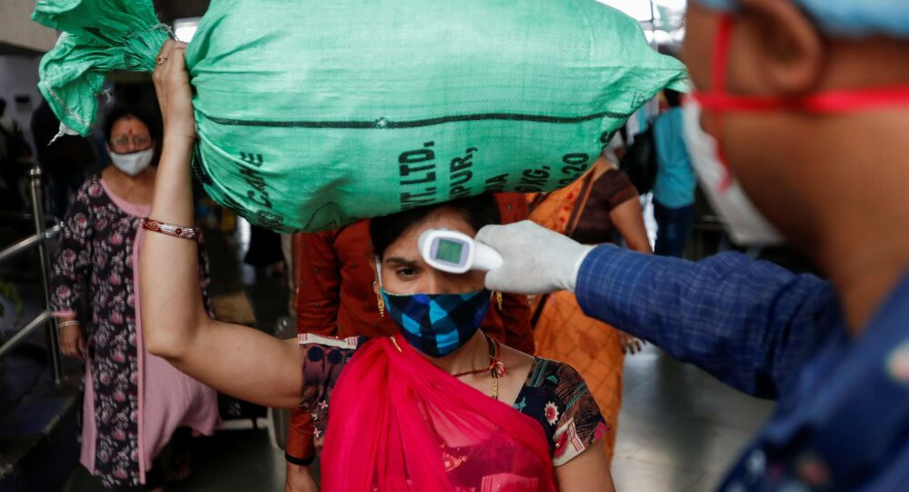 A health worker checks the temperature of a passenger, amid the spread of the coronavirus disease (COVID-19), at a railway station in Mumbai, India, March 17, 2021