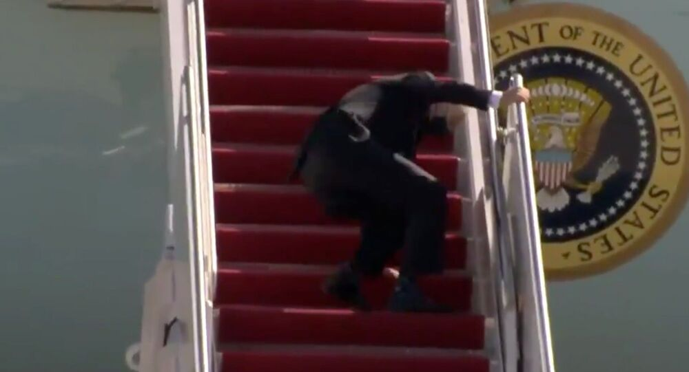 Screenshot captures the moment that US President Joe Biden caught himself after stumbling three times while ascending the airstairs to board Air Force Once.