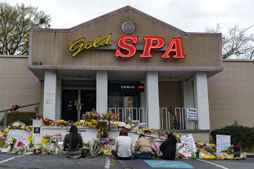 People bring flowers to the memorial sight set up outside of The Gold Spa on 19 March 2021 in Atlanta, Georgia.