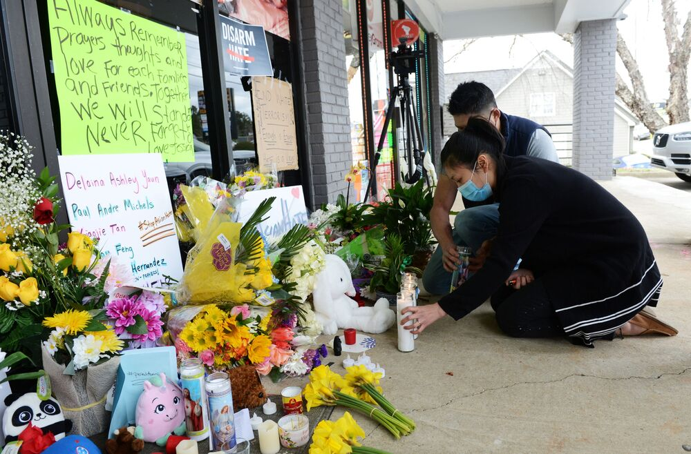 Jami Webb and her fiance Kevin Chen light candles outside Young's Asian Massage following the deadly shootings in Acworth, Georgia, US 19 March 2021. Webb is the daughter of Xiaojie Tan, the owner of the spa who was killed in the shootings.