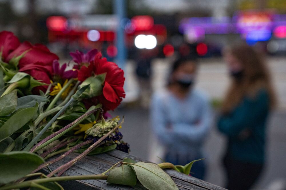 People bring flowers to the memorial site set up outside of The Gold Spa on 19 March 2021 in Atlanta, Georgia.
