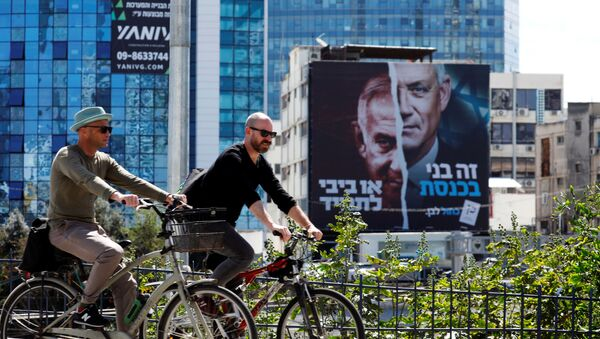 People cycle next to a Blue and White party election campaign banner depicting its leader, Israeli Defence Minister Benny Gantz, alongside Israeli Prime Minister Benjamin Netanyahu ahead of the March 23 ballot, in Tel Aviv, Israel March 17, 2021.  - Sputnik International