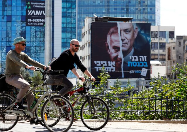 People cycle next to a Blue and White party election campaign banner depicting its leader, Israeli Defence Minister Benny Gantz, alongside Israeli Prime Minister Benjamin Netanyahu ahead of the March 23 ballot, in Tel Aviv, Israel March 17, 2021.