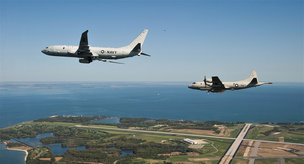 The first P-8A Poseidon test aircraft, followed by its propeller-driven P-3C predecessor, flies past NAS Patuxent River. File photo.