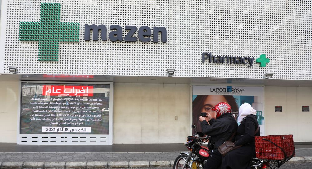 People sit on a motorbike outside a closed pharmacy, as pharmacies went on strike on Thursday, in Beirut, Lebanon March 18, 2021.