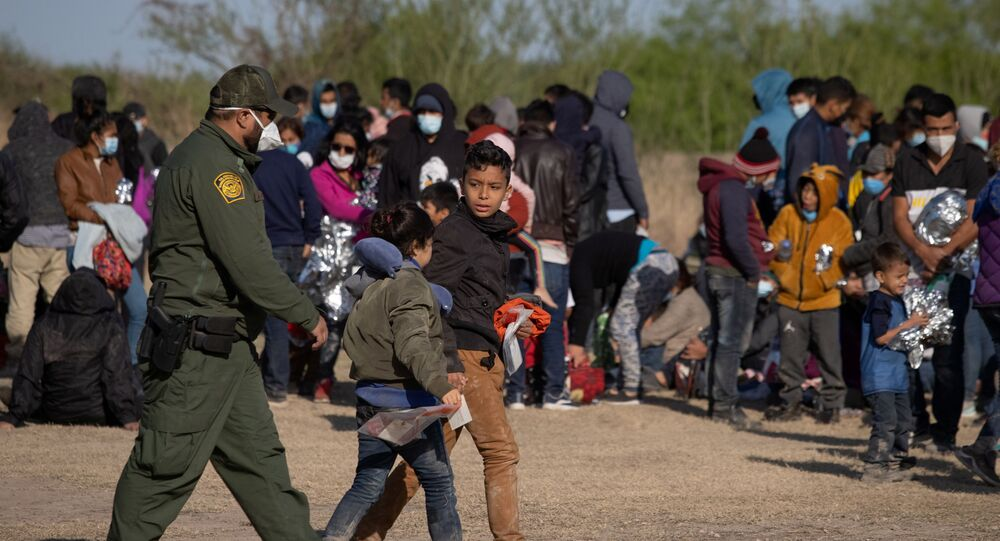 A U.S. Border Patrol Agent escorts two asylum-seeking unaccompanied minors from Central America as others take refuge near a baseball field after crossing the Rio Grande river into the United States from Mexico on rafts, in La Joya, Texas, U.S., March 19, 2021.