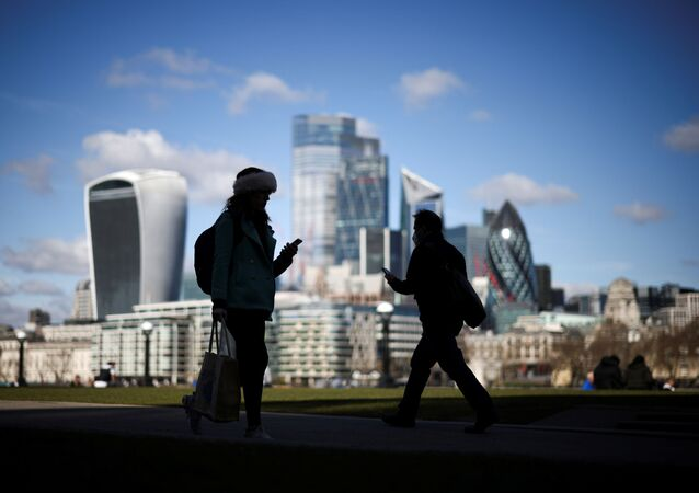 The City of London financial district can be seen as people walk along the south side of the River Thames, amid the coronavirus disease (COVID-19) outbreak in London, Britain, March 19, 2021
