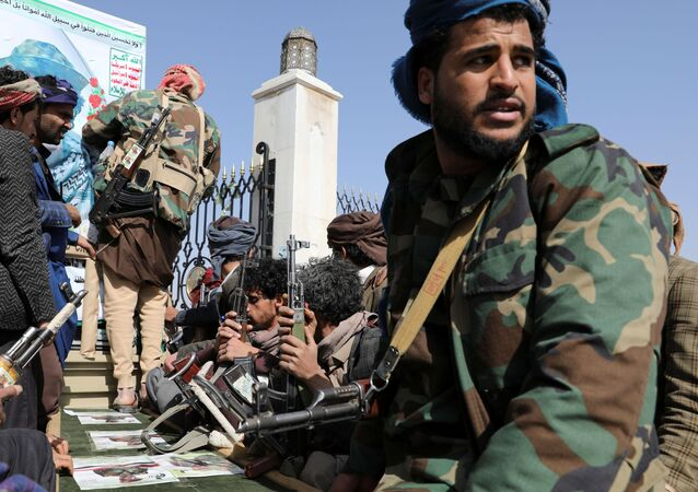 Armed Houthi followers sit next to a coffin of a Houthi fighter killed in recent fighting against government forces in Yemen's oil-rich province of Marib, during a funeral procession in Sanaa, Yemen February 20, 2021.
