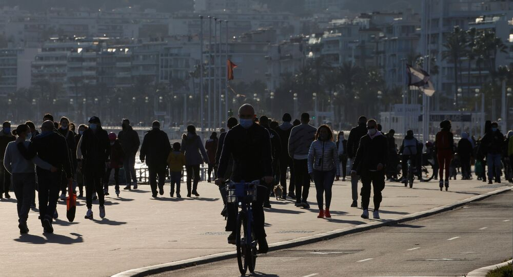 People walk and cycle on the Promenade des Anglais in Nice, as France's 16 hardest-hit departments go into a new month-long lockdown imposed to slow the rate of the coronavirus disease (COVID-19) contagion, France March 20, 2021.