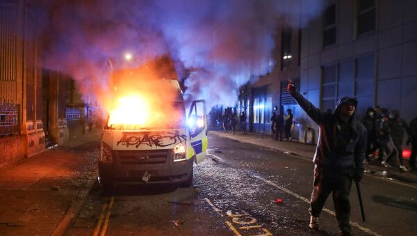A demonstrator gestures near a burning police vehicle during a protest against a new proposed policing bill, in Bristol, Britain, March 21, 2021. - Sputnik International