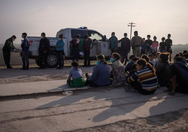 A U.S. Border Patrol agent processes asylum-seeking unaccompanied minors as family units sit on the sideline after about 70 migrants crossed the Rio Grande river into the United States from Mexico on a raft in Penitas, Texas, U.S., March 17, 2021.