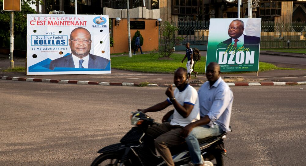 Men on a motorbike ride past billboards of presidential candidates and leading opposition leaders Guy Brice Parfait Kolelas and Mathias Dzon, in Brazzaville, Republic of Congo, 17 March  2021
