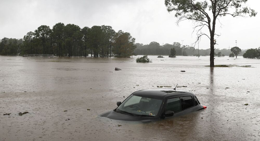 A partially submerged car is seen abandoned in floodwaters in the suburb of Windsor as the state of New South Wales experiences widespread flooding and severe weather, in Sydney, Australia, March 22, 2021