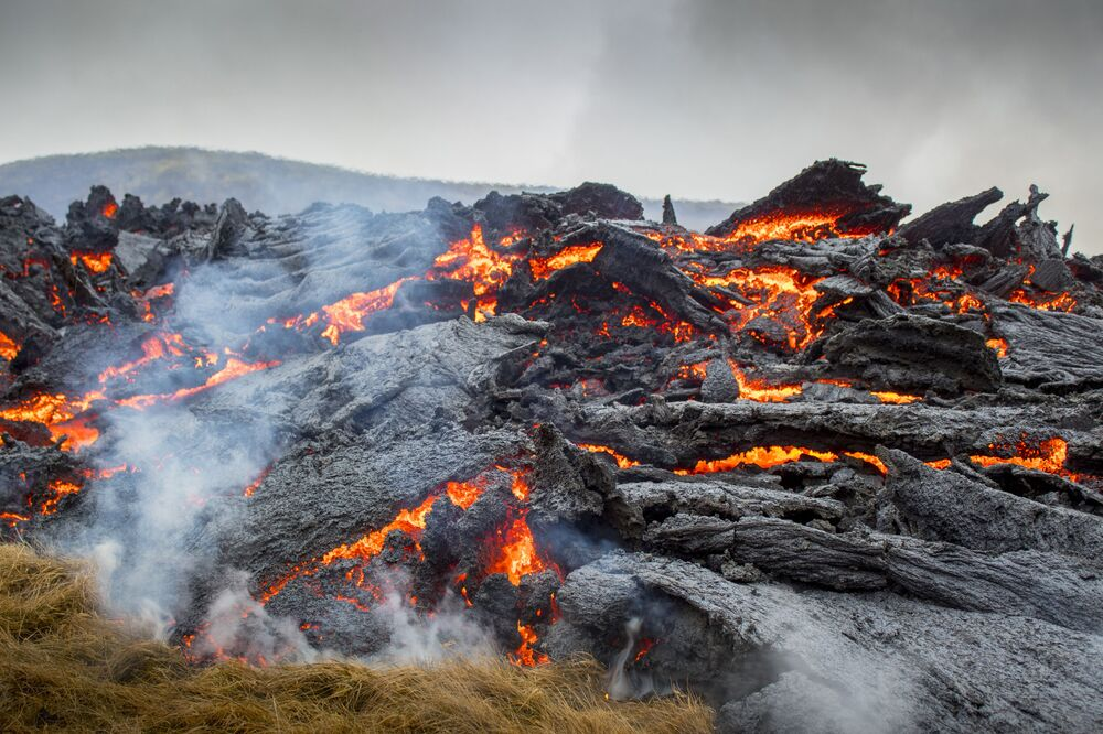 Lava flows from an eruption of a volcano on the Reykjanes Peninsula in southwestern Iceland on Saturday, 20 March 2021. The eruption of the long-dormant volcano that sent streams of lava flowing across a small valley in Iceland is easing and shouldn't interfere with air travel, the Icelandic Meteorological Office said Saturday.
