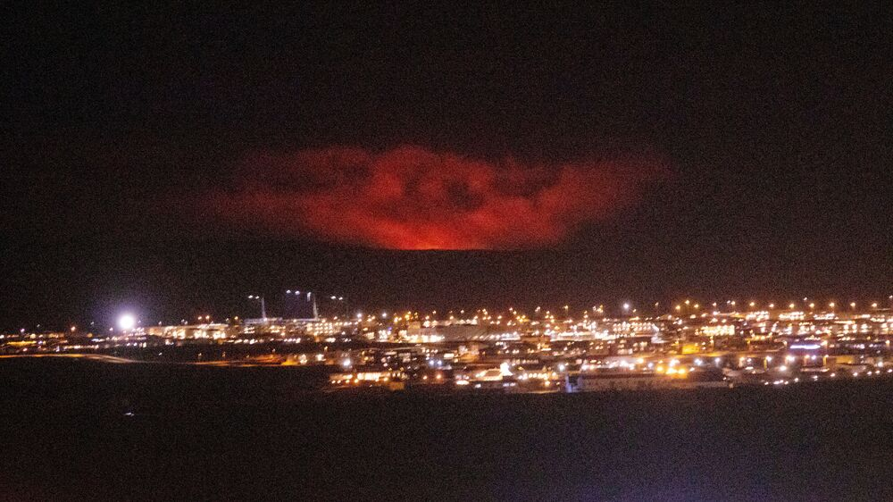 A volcanic eruption is seen (rear) near Fagradalsfjall, a mountain on the Reykjanes Peninsula, Iceland 19 March 2021, in this picture obtained from social media.