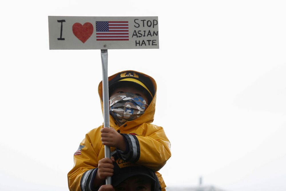 A child holds a sign with a US flag at a Stop Asian Hate rally and vigil to remember the Atlanta shooting victims at Downtown Park in Bellevue, Washington, 20 March 2021.