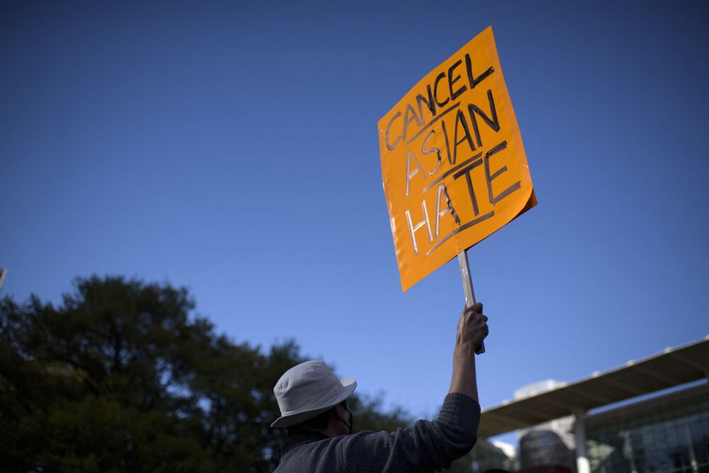 A man holds up a sign during a Stop Asian Hate rally at Discovery Green in downtown Houston, Texas on 20 March 2021.