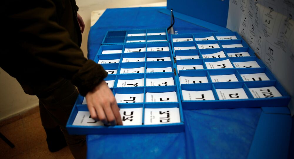 An Israeli soldier sorts ballot papers at a mobile voting booth set-up for soldiers to cast their early vote in the March 23 general election, amid the coronavirus disease (COVID-19) crisis, at a military base, near Kibbutz Regavim, Israel March 17, 2021.