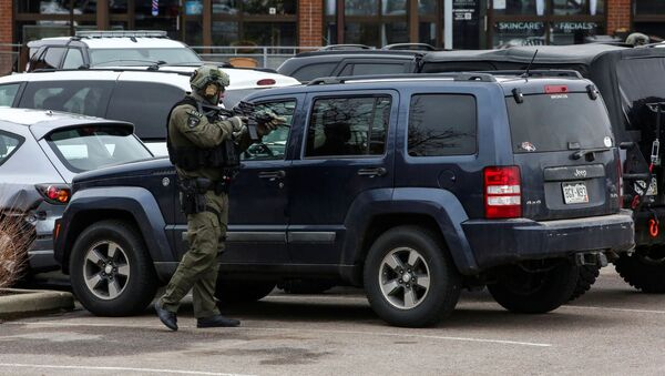 Law enforcement officers sweep the parking lot at the site of a shooting at a King Soopers grocery store in Boulder, Colorado, U.S. March 22, 2021. - Sputnik International
