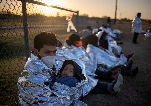 Dustin, an asylum-seeking migrant from Honduras, holds his six-year-old son Jerrardo, 6, as they awake at sunrise next to others who took refuge near a baseball field after crossing the Rio Grande river into the United States from Mexico on rafts, in La Joya, Texas, U.S., March 19, 2021. Emergency blankets were provided to the group of about 150 migrants from Central America by the U.S. Border Patrol agents.