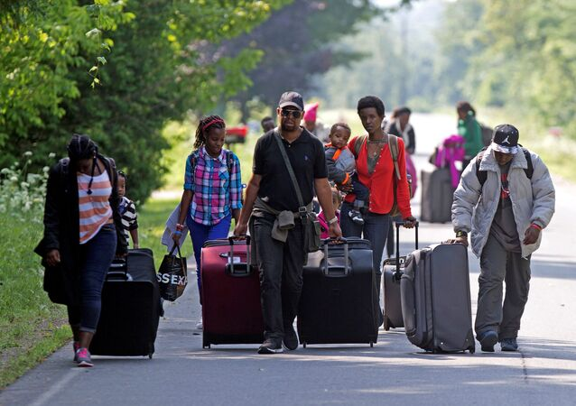 Three families that claimed to be from Burundi walk down Roxham Road to cross into Quebec at the US-Canada border in Champlain, New York,  August 3, 2017