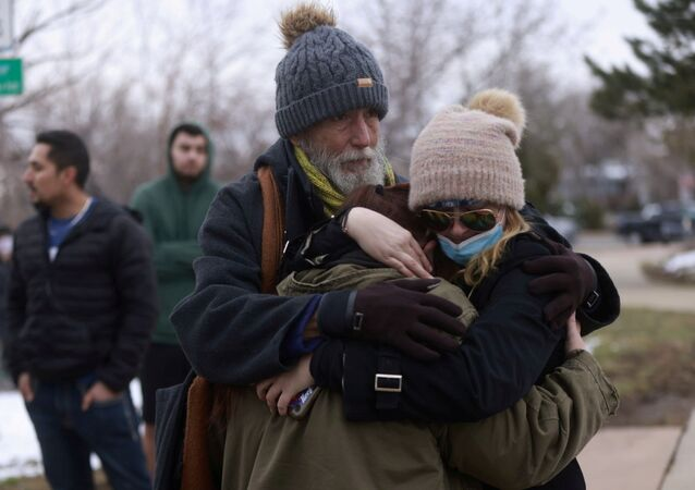 Sarah Moonshadow is comforted by David and Maggie Prowell after being inside a King Soopers grocery store during a shooting in Boulder, Colorado, 22 March 2021.