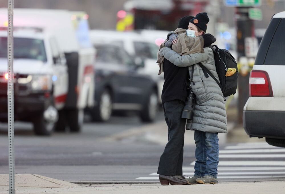 Women hug on the corner of Broadway and Table Mesa Drive near a King Soopers grocery store where a shooting took place, Monday, 22 March 2021, in Boulder, Colorado.