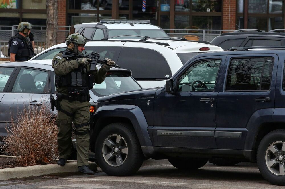 Law enforcement officers sweep the parking lot at the site of a shooting at a King Soopers grocery store in Boulder, Colorado, 22 March 2021.