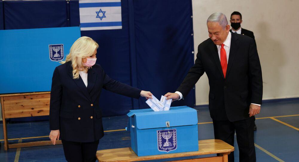 Israeli Prime Minister Benjamin Netanyahu and his wife Sara cast their ballots at a polling station as Israelis vote in a general election, in Jerusalem March 23, 2021