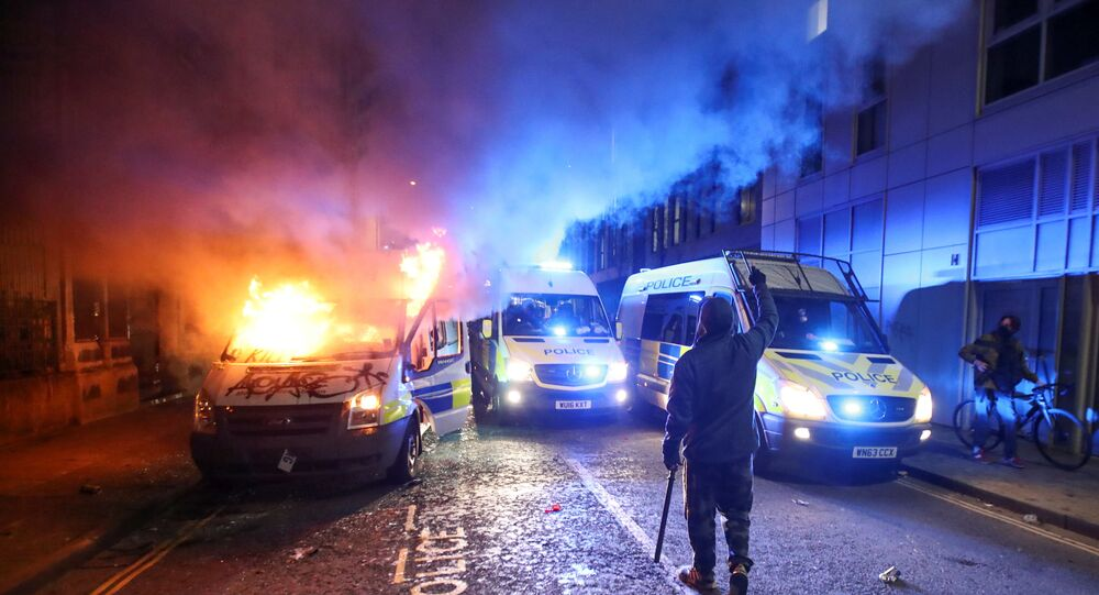 A demonstrator gestures near a burning police vehicle during a protest against a new proposed policing bill, in Bristol, Britain, March 21, 2021.