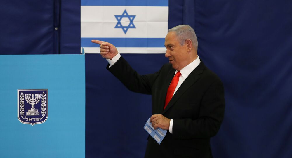 Israeli Prime Minister Benjamin Netanyahu gestures while standing near a voting booth as he prepares to cast his ballot in Israel's general election, at a polling station in Jerusalem, 23 March 2021