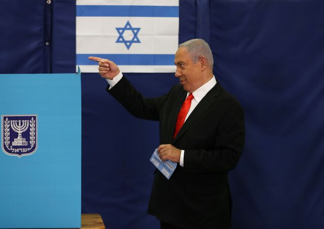Israeli Prime Minister Benjamin Netanyahu gestures while standing near a voting booth as he prepares to cast his ballot in Israel's general election, at a polling station in Jerusalem March 23, 2021