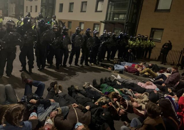 Police officers stand in position as protesters demonstrate against new policing laws in Bristol, Britain, early March 24, 2021