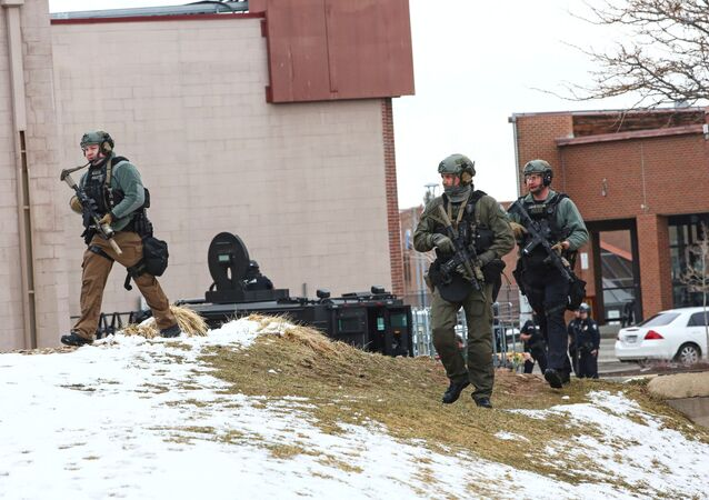 Law enforcement officers sweep the area outside of a King Soopers grocery store, which was the site of a shooting in Boulder, Colorado, U.S. March 22, 2021