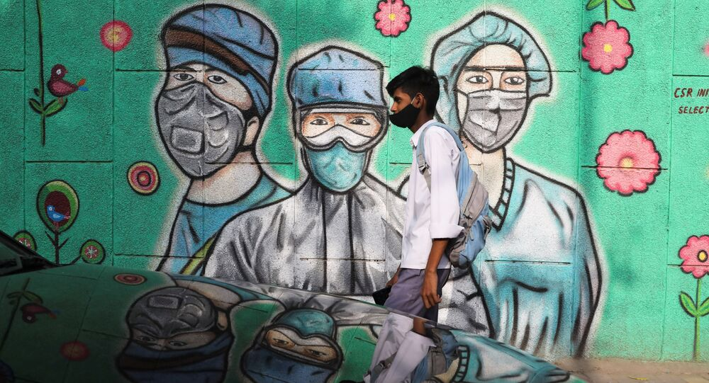 A boy walks past a graffiti amidst the spread of the coronavirus disease (COVID-19) on a street in New Delhi, India, March 22, 2021
