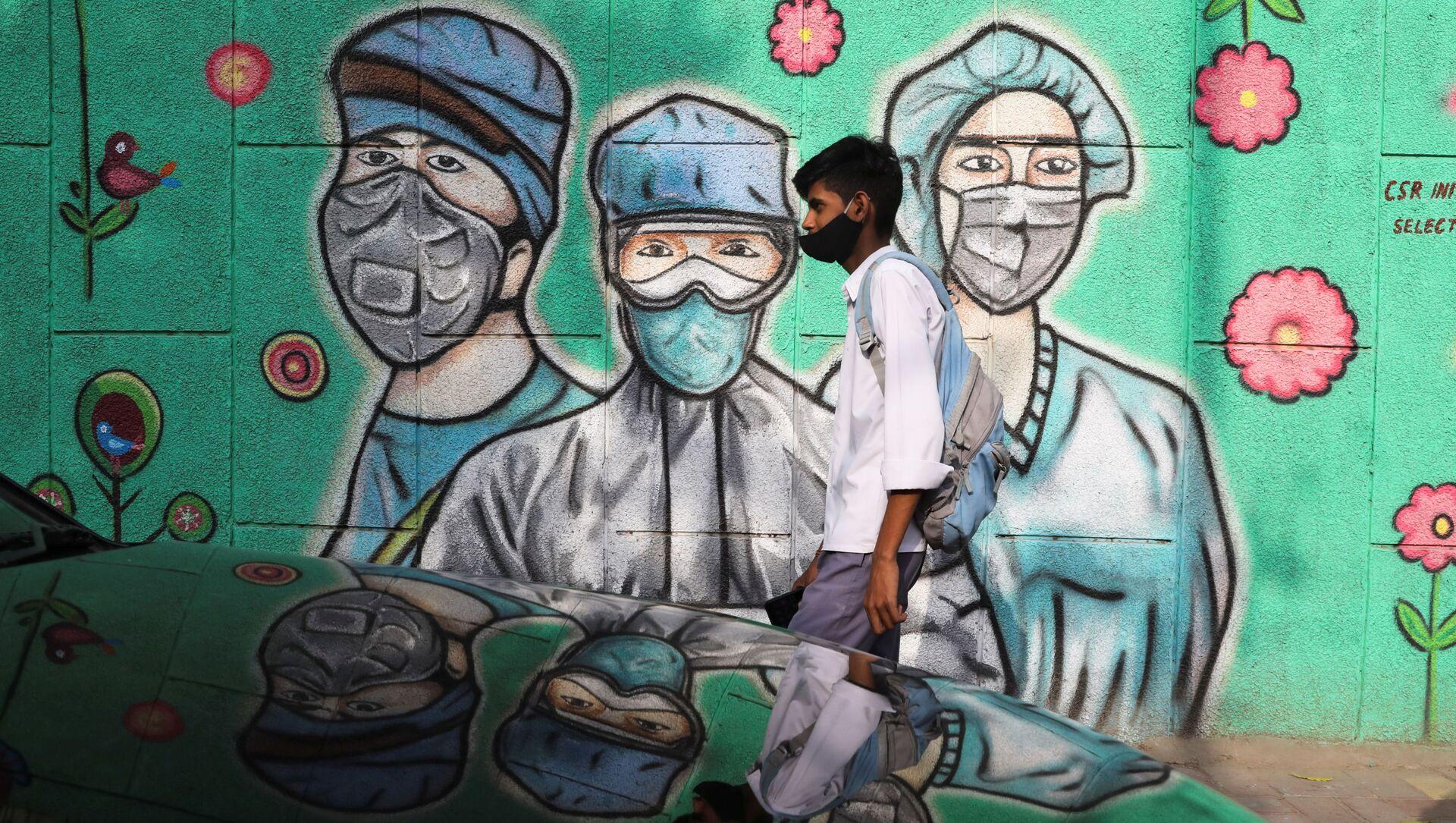 A boy walks past a graffiti amidst the spread of the coronavirus disease (COVID-19) on a street in New Delhi, India, March 22, 2021 - Sputnik International, 1920, 24.03.2021
