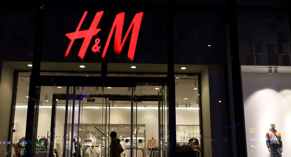 A woman enters a branch of Swedish fashion retailer H&M at a shopping mall in Beijing, China, 24 March 2021.