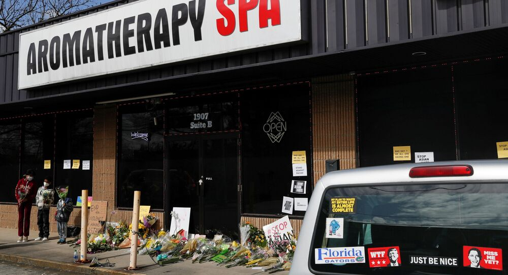 Children holding flowers stand during a vigil at a makeshift memorial outside the Aromatherapy Spa following the deadly shootings in Atlanta, Georgia, U.S. March 21, 2021