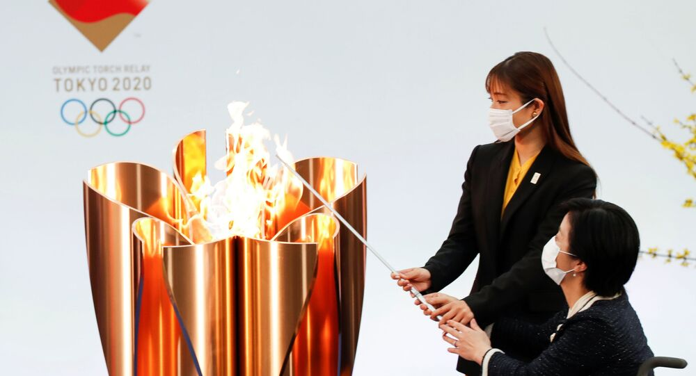 Actor Satomi Hishihara and Paralympian Aki Taguchi light the celebration cauldron on the first day of the Tokyo 2020 Olympic torch relay in Naraha, Fukushima prefecture, Japan March 25, 2021