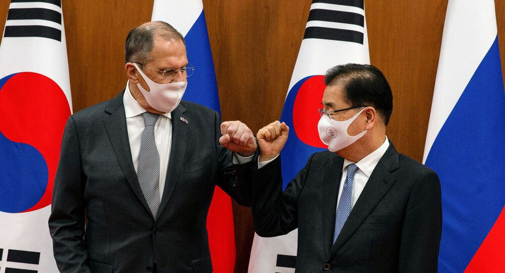 Russian Foreign Minister Sergei Lavrov (L) bumps elbows with his South Korean counterpart Chung Eui-yong before their meeting at the foreign ministry in Seoul, South Korea, March 25, 2021