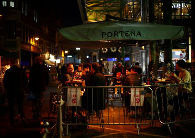FILE PHOTO: People drink outside a bar as the spread of the coronavirus disease (COVID-19) continues, in London, Britain, December 15, 2020