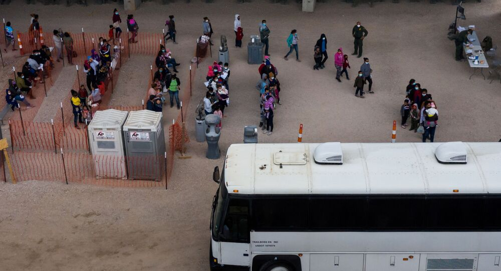 Asylum seeking migrant families from Central America line up to be transported from a make shift U.S. Customs and Border Protection processing center under the Anzalduas International Bridge after crossing the Rio Grande river into the United States from Mexico in Granjeno, Texas, U.S., March 24, 2021