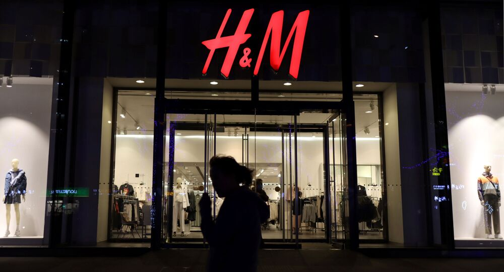 A woman walks past a store of the Swedish fashion retailer H&M at a shopping mall in Beijing China