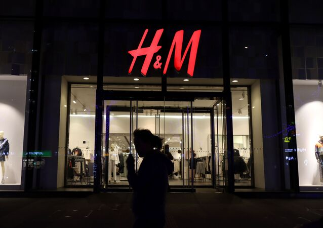 A woman walks past a store of the Swedish fashion retailer H&M at a shopping mall in Beijing, China March 24, 2021