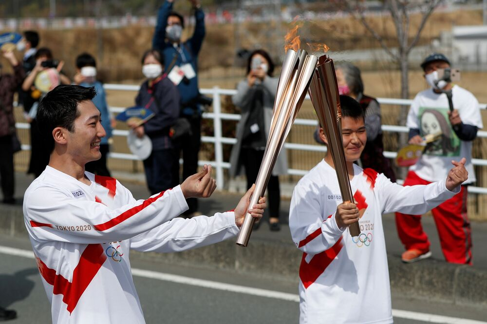 Torchbearers pose during the Tokyo 2020 Olympic torch relay on the first day of the relay in Naraha, Fukushima prefecture, Japan, 25 March 2021.