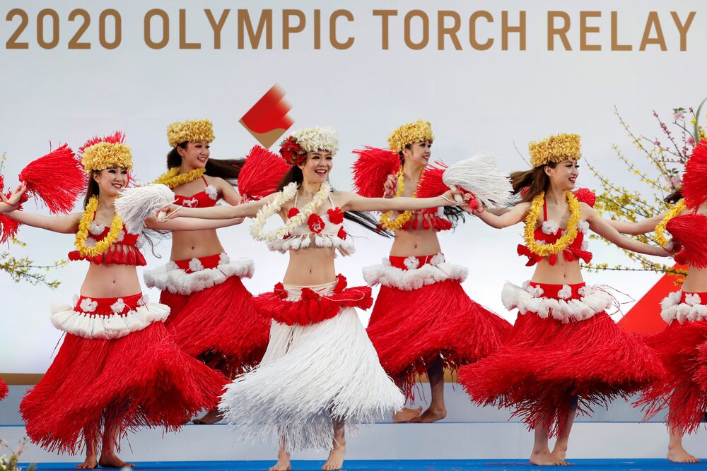Members of the Spa Resort Hawaiians Dancing Team Hula Girls during an opening performance on the first day of the Tokyo 2020 Olympic torch relay in Naraha, Fukushima prefecture, Japan, 25 March 2021.
